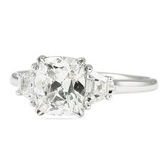 Custom handmade three stone engagement ring design with antique cushion cut center offset by step cut trapezoid side diamonds; handmade in white gold.  Ring was designed to allow for a flush fitting eternity band