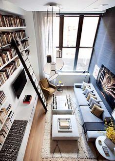 sala de estar pequena decorada com  sofá baixo cinza, prateleiras com livros na parede da televisão, luminárias pendentes de teto e duas mesas de centro baixas