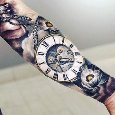 Coloured pocketwatch, chains and flowers tattoo sleeve on lower arm Más