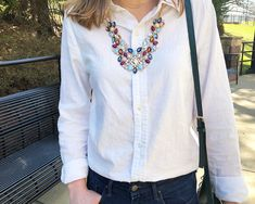 Molly's white linen button down is a great basic staple. She pairs it with a dramatic gold necklace full of navy, baby blue, and maroon jewels.