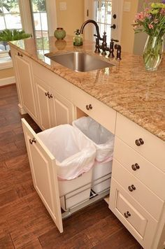 Remodeled kitchen with cabinet drawer for waste and recyclable baskets by Neal's Design Remodel. #remodelingkitchen