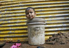 A boy sits in a bucket as he plays in Chennai, India, on Dec. 30 (© Babu/Reuters)