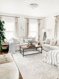 Bright white interior living room with neutral, minimal farmhouse accents. Off white drapes and striped throw blankets. Brown and black coffee table.