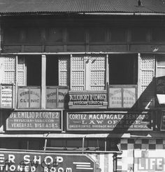 A view of doctor offices house on Carriedo Street in Manila. Location:	Manila, Philippines Date taken:	1942 Photographer:	Carl Mydans