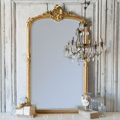 Eloquence, Inc. Antique French Mirror: 1900 Grand gilt French antique mirror that features a beautiful scallop shell motif at the crown. Corners and middle of the frame also boast ornate details, as well as lovely beading around the central edge of the frame. Beveled glass and hints of deep red peeking through the gilt make this a luxury item for any space.