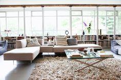"""Denna moderna glasvägg förnekar att den är en vägg! Den synliga träbjälken """"svävar"""" på ett antal tunna, runda, vita stålpelare"""