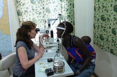 Dr. Joseph examining a patient's eyes in Ganta, Liberia. #givesight www.seeintl.org