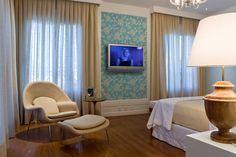 cortinas, abajur de madeira, lustre de cristal, poltrona e rodapé