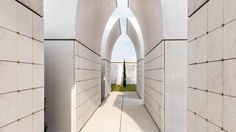 CN10 Architetti has built a trio of white concrete and marble funerary arches with space to host ossuaries and cinerary urns for a cemetery in Bergamo