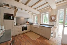 Cream kitchen with granite worktops in country kitchen with tiled floor and ceiling beams painted to match the colour scheme.