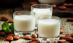 Almond milk in small glasses and spilled dry almonds on old wooden background, selective focus