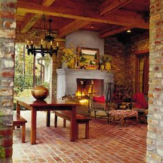 Breezy Porches and Patios | Cozy Brick Porch | SouthernLiving.com-Composed of a brick chimney, mantel, and firebox, this exterior fireplace is covered with stucco. This touch not only distinguishes it from the surrounding brick walls, but it also makes a focal point. The hearth is raised for additional seating.