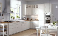 Traditional kitchen with white cabinets, wood worktops, glass doors and integrated appliances