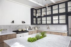 A London Home Full of Light// modern kitchen, tile behind glass cabinets, subway tile