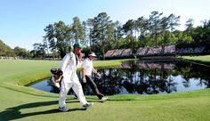 Phil Mickelson and caddie Jim Mackay walk to the 15 green during Saturday's third round of the 2012 Masters Tournament at Augusta National Golf Club on April 7, 2012