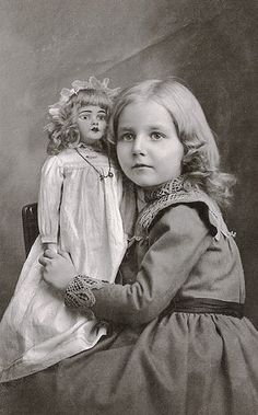 Girl with elaborate collar and cuffs, with her doll c. 1918.