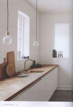 Witte, minimalistische keuken met houten visgraat blad.