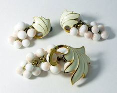 """Alice Caviness Enamel Leaves Glass Beaded Demi Parure, Clip Earrings. Set in gold tone metal. Signed Alice Caviness on earrings only. This has ivory colored enamel on gold leaves and glass beads that look almost like angel skin coral. The beads resemble grape clusters. Beautiful set. The brooch measures 2 3/4"""" and the clip earrings are 1 3/4"""". Very good vintage condition with slight discoloration on the back of the earrings. circa 1950's."""