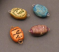 DIY Clay Beads ~ made over a paper clip! - Roll polymer clay around wire then impress images with rubber stamps. After baking, fill in the stamped areas with paint and wipe away the excess. When the paint is dry apply Distress Inks and heat set.  Viola!
