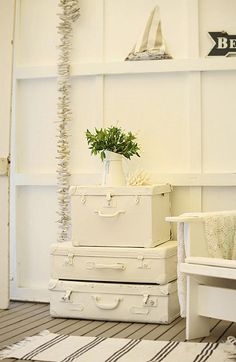 A vignette of vintage luggage painted in white pilled on top of each other. So charming! Via A Beach Cottage.