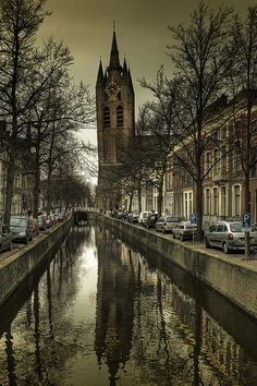 The Oude Kerk, Oude Jan, Delft, Netherlands' clock tower is reflected in the water below...