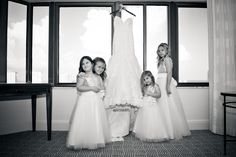 Photo by Michelle Lawson Photography. My junior bridesmaids and flowergirls standing with my Maggie Sottero designer dress hanging in the window. Behind the scenes pic of getting dressed! #wedding #weddingideas #gettingdressed #weddingdress #behindthescenes #juniorbridesmaid #flowergirls #weddingdress #weddingdressideas #mstriciasfl #gettingready #blushweddingdress #pinkweddingdress #MaggieSottero #designerweddingdress #blackandwhiteweddingphotography
