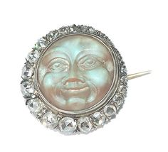 "A brooch, set with a carved moonstone ""man in the moon"" face, with a diamond crescent, set in silver topped gold, silver, or platinum, circa 1900."