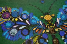 detail from a framed & glazed vintage wool work in shades of blue & purple on a green background featuring a butterfly