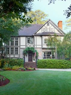 paint shades make this Tudor stand out in the crowd. Stucco: Sag Harbor Gray, Trim: Gloucester Sage (both by Benjamin Moore). A mortar wash gave the original bricks a pretty, aged patina, and the coordinating roof tiles tie the whole look together.