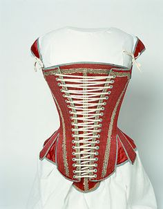 Extant English stays, dated 1620-1640. Linen and red silk sating edged with pale blue ribbons. Laced in the front over a boned stomacher. (Possibly of a later date?)
