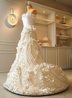 This stunning wedding dress cake is truly food as art. It is so intricately decorated that it almost appears wearable. The bodice is designed simply with a few details while the skirt is covered in swirls, ridges, and calla lilies. This wedding dress cake almost looks good enough to wear.