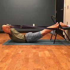 #salabhasana variation. Feet up on chair- increases backbend in low back and decreases effort. Hands interlaced behind head. Two 12 foot straps attached to forearms and linked to dowel at chair increases backbend in top back/decreases effort. @bparedc