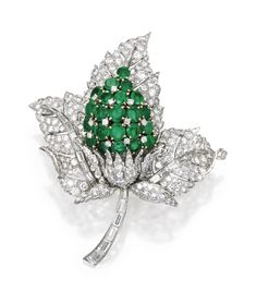 Platinum, 18 Karat Gold, Emerald and Diamond Brooch - The stylized flower centered by a cluster of round emeralds weighing approximately 6.00 carats, further set with numerous round, baguette and single-cut diamonds weighing approximately 10.60 carats.