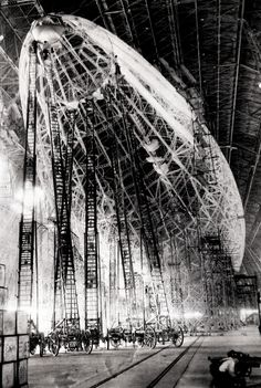 Men atop giant fire ladders work on airship