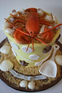 AMAZING! this lobster topped sand bucket was the center of a summer birthday celebration. We hand crafted the lobster from sugar paste and the beach bucket is entirely cake.  Chocolate shells are scattered throughout. #summer #beach