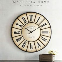 This striking oversized clock from the Magnolia Home Collection by Joanna Gaines is sure to be a handsome statement piece and will add a welcoming ambience to your room, too. It features a classic round shape, Magnolia Clock Company logo and raised Roman numerals.