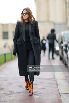 Christine Centenera wears a black coat, a lace black top, black pants, silver sunglasses, and flower print boots, outside the Hermes show, during Paris Fashion Week Womenswear Fall/Winter 2017/2018, on March 6, 2017 in Paris, France.