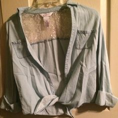 Light blue shirt This shirt is a light blue, washed out Jean color. It has white lace across the back and ties in the front as well as buttons down. It is pictured with the sleeves rolled up but they roll down also. I've only worn this once so it's in really good condition! Candie's Tops Button Down Shirts