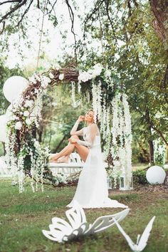 an oversized grapevine wreath with greenery and white blooms used as a swing