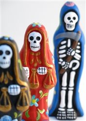 Brightly coloured wooden masks decorated in a style reminiscent of candy skulls which are made to celebrate Día de Muertos, the Mexican Day of the Dead Holiday.