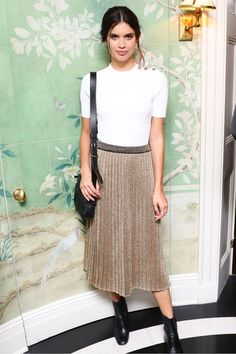 Sara Sampaio in a white tshirt with metallic pleated skirt and black ankle boots