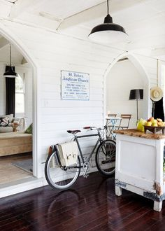 This relaxed kitchen is effortlessly chic with white walls, dark wooden floors, and a wood covered center island. We just love the bicycle too!