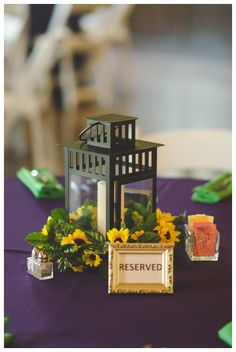 small metal lanterns are circled with yellow flower garland on top of deep plum table cloths - thereddirtbride.com - see more of this wedding here