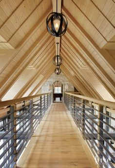 The expansive second-floor walkway creates a sense of being suspended in the air. The bridge connects the two ends of the house and leads to the upstairs bedrooms and bunkroom. Light fixtures from Uttermost complement the metal railings. #ModernFarmhouse