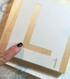 Pressing down Con-Tact Paper for a good seal to prevent bleeding underneath Scrabble Kunst, Scrabble Tile Wall Art, Scrabble Tile Crafts, Scrabble Letters, Scrabble Board, Do It Yourself Furniture, Diy Furniture, Diy Tuiles, Home Crafts