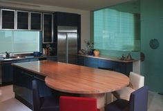 Rectangular kitchen island with a round table and colorful chairs