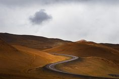 A winding road embedded in a beautiful hilly landscape of Iceland.