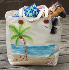 Hand painted with a beach scene including sand, starfish, palm tree with coconuts, the ocean and some flying birds using All-Purpose Inks, a canvas tote is full of supplies ready to head to the beach. Painted Canvas Bags, Jute Bags, Beach Tote Bags, Fabric Painting, Bag Making, Purses And Bags, Ink Stains, Reusable Tote Bags, Flying Birds