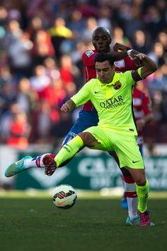 Xavi Hernandez (R) of FC Barcelona competes for the ball with Allan Nyom (L) of Granada CFduring the La Liga match between Granada CF and FC Barcelona at Nuevo Estadio de los Carmenes on February 28, 2015 in Granada, Spain.