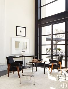 Photo works by Susan Derges (top) and Miriam Böhm overlook a seating area with vintage Pierre Jeanneret armchairs.